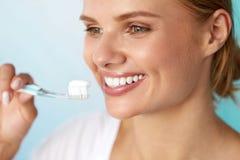 Kvinna med härligt leende som borstar sunda vita tänder Fotografering för Bildbyråer