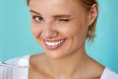 Kvinna med härligt leende, sunda vita tänder med tandborsten Fotografering för Bildbyråer