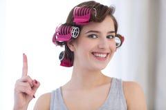 Kvinna med hårrullar på hennes head peka finger upp Arkivfoto