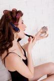 Kvinna med hårrullar som talar på telefonmakeupen royaltyfri bild