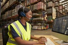 Kvinna med hörlurar med mikrofon som arbetar i på plats kontor av ett lager royaltyfri foto