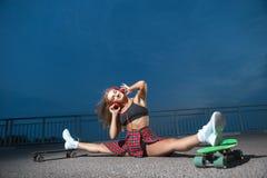 Kvinna med hörlurar och skateboarder royaltyfria foton