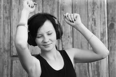 Kvinna med hörlurar som lyssnar till musik, Royaltyfri Fotografi