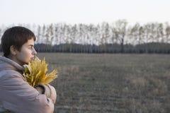 Kvinna med höstliga sidor i fält Royaltyfria Bilder