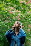 Kvinna med h?rlurar p? blomningtr?d p? bakgrund royaltyfria foton