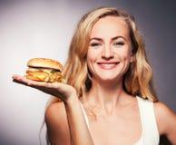 Kvinna med hamburgaren royaltyfria bilder
