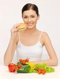Kvinna med hamburgaren och grönsaker Arkivbild