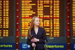 Kvinna med handbagage i terminalen för internationell flygplats som ser informationsbrädet arkivfoton