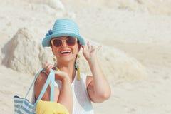 Kvinna med handdukpåsen på den sandiga stranden Royaltyfri Foto