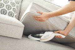 Kvinna med handheld vakuumlokalvård på soffan arkivbilder