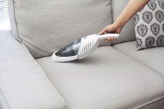 Kvinna med handheld vakuumlokalvård på soffan arkivbild