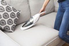 Kvinna med handheld vakuumlokalvård på soffan fotografering för bildbyråer