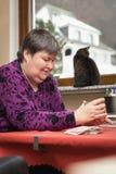 Kvinna med handikapp att framkalla spela kort, gyckel och att studera arkivfoto