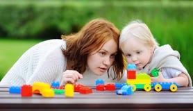 Kvinna med hans son som spelar med färgrika plast- kvarter Royaltyfri Foto