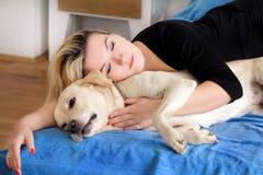 Kvinna med hemmastadd gullig hundkapplöpning Stilig flicka som vilar och sover med hennes hund i säng i sovrum Ägare och hund som arkivbild