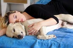 Kvinna med hemmastadd gullig hundkapplöpning Stilig flicka som vilar och sover med hennes hund i säng i sovrum Ägare och hund som royaltyfri bild