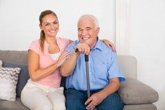 Kvinna med henne rörelsehindrad fader Sitting On Sofa arkivbild