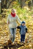 Kvinna med henne son som gör fruktträdgården i höst arkivfoton