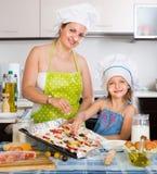 Kvinna med hennes dotter som förbereder piza Arkivbilder