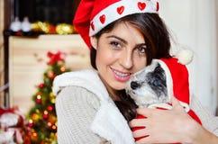 Kvinna med hennes hund med röda julhattar Arkivfoton