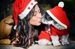Kvinna med hennes hund med röda julhattar Fotografering för Bildbyråer