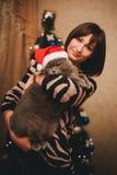 Kvinna med hennes katt som bär den Santa Claus hatten nära julträd Royaltyfri Foto