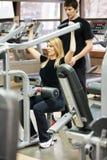 Kvinna med hennes personliga konditioninstruktör i idrottshallen fotografering för bildbyråer