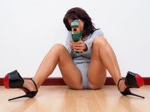 Kvinna med höga häl som siktar med leksakvapnet Arkivbild