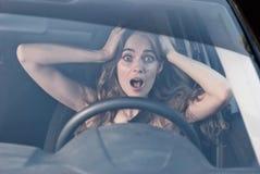 Kvinna med händer på att sitta för ögon som skrämmas i bil Arkivfoto