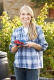 Kvinna med home-grown frukt Arkivfoto