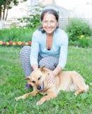 Kvinna med hunden i gård Royaltyfri Bild