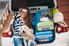 Kvinna med hunden med bilen mycket av resväskor Royaltyfri Fotografi