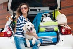 Kvinna med hunden med bilen mycket av resväskor Royaltyfri Bild