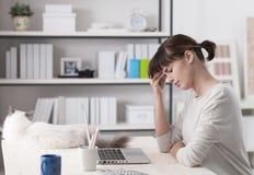 Kvinna med huvudvärksammanträde på skrivbordet royaltyfria foton