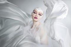 Kvinna med idérikt smink i ett vitt torkdukeflyg En flicka som rymmer en flygvittorkduk royaltyfri foto