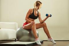 Kvinna med idrottshallbollen och hantel som gör övning Royaltyfri Fotografi