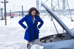 Kvinna med ilska som ser motorn av hennes bil ett brutet Arkivfoto