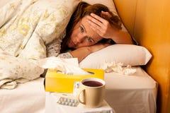 Kvinna med influensa som vilar i säng arkivfoton