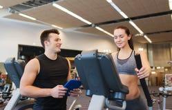 Kvinna med instruktören som övar på gradvist i idrottshall Royaltyfri Bild