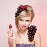Kvinna med jordgubbar och gruppen av druvor Royaltyfri Bild