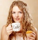Kvinna med kaffe och kakan arkivbild
