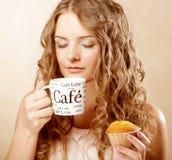 Kvinna med kaffe och kakan arkivfoto