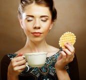 Kvinna med kaffe och kakor Arkivbild