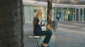 Kvinna med kaffe och minnestavlan på bänk Sidosikt av formellt kvinnasammanträde med minnestavlan på bänk och drickakaffe arkivfilmer
