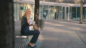 Kvinna med kaffe och minnestavlan på bänk Sidosikt av formellt kvinnasammanträde med minnestavlan på bänk och drickakaffe stock video