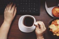 Kvinna med kaffe som äter skräpmat på arbetsplatsen Arkivbilder
