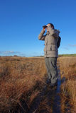 Kvinna med kikare som birdwatching, Royaltyfria Bilder