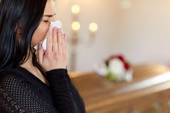 Kvinna med kistagråt på begravningen i kyrka Royaltyfri Bild