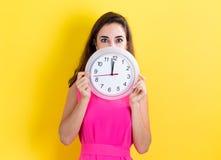 Kvinna med klockan som visar nästan 12 Royaltyfri Foto