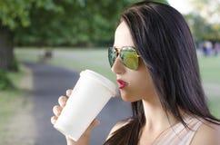 Kvinna med koppen kaffe i en parkera Royaltyfria Bilder